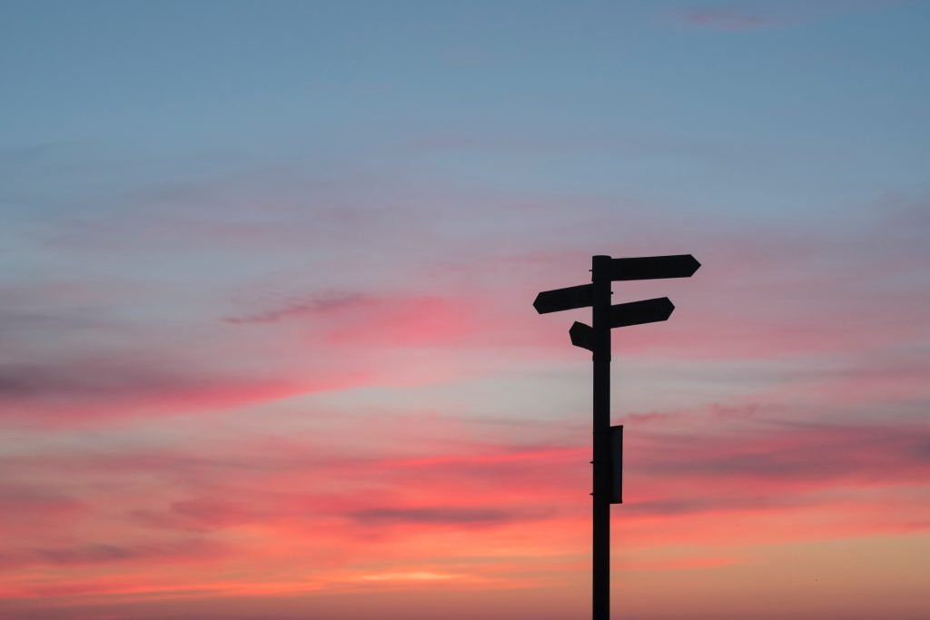 A signpost pointing in many directions during sunset.