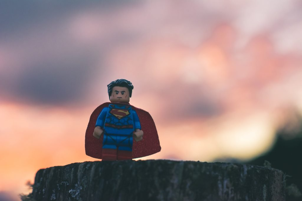 A Lego Superman standing on a tree stump at dusk.