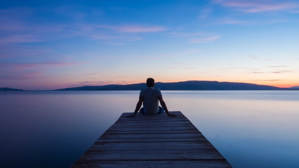 A person sitting on a dock at sunset.
