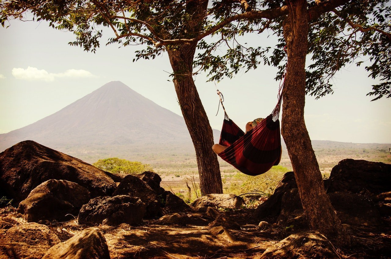 Person laying in a hammock between two trees. There is a mountain off in the distance.