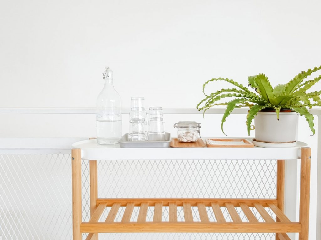 A white-topped bar cart sitting in a bright kitchen. There is a healthy plant and drinking glasses sitting on the cart.