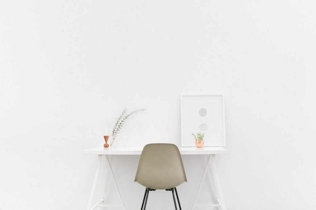 A beige chair sitting at a white desk against a white wall.