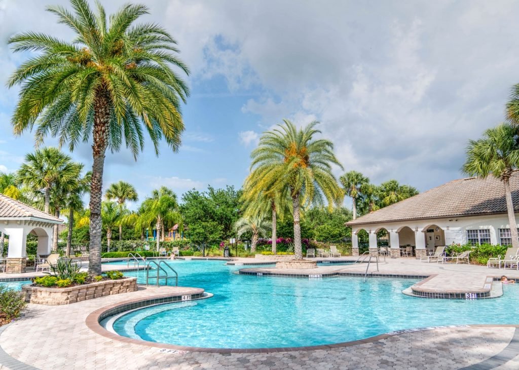 Backyard pool surrounded by palm trees and cabanas. The sky is partly cloudy but it looks warm out.