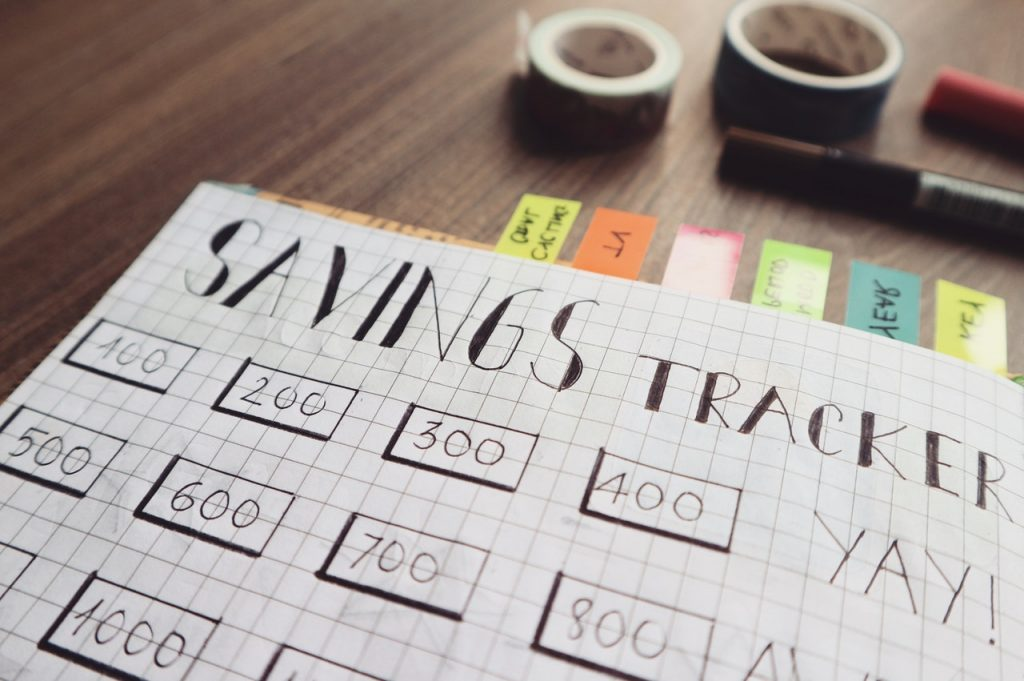 A grid-style notebook with the words Savings Tracker at the top. The notebook is used to keep track of savings goals.