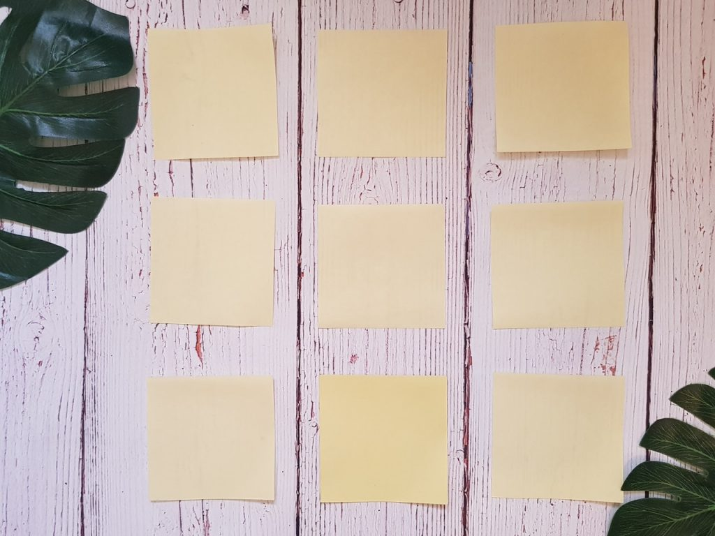 Three rows of three sticky notes on a white wooden table.