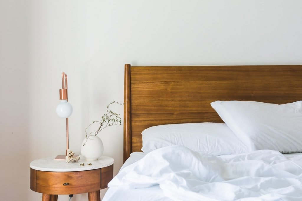 White sheets laying on a wooden bed frame. A copper lamp sits on top of a wooden side table next to the bed.