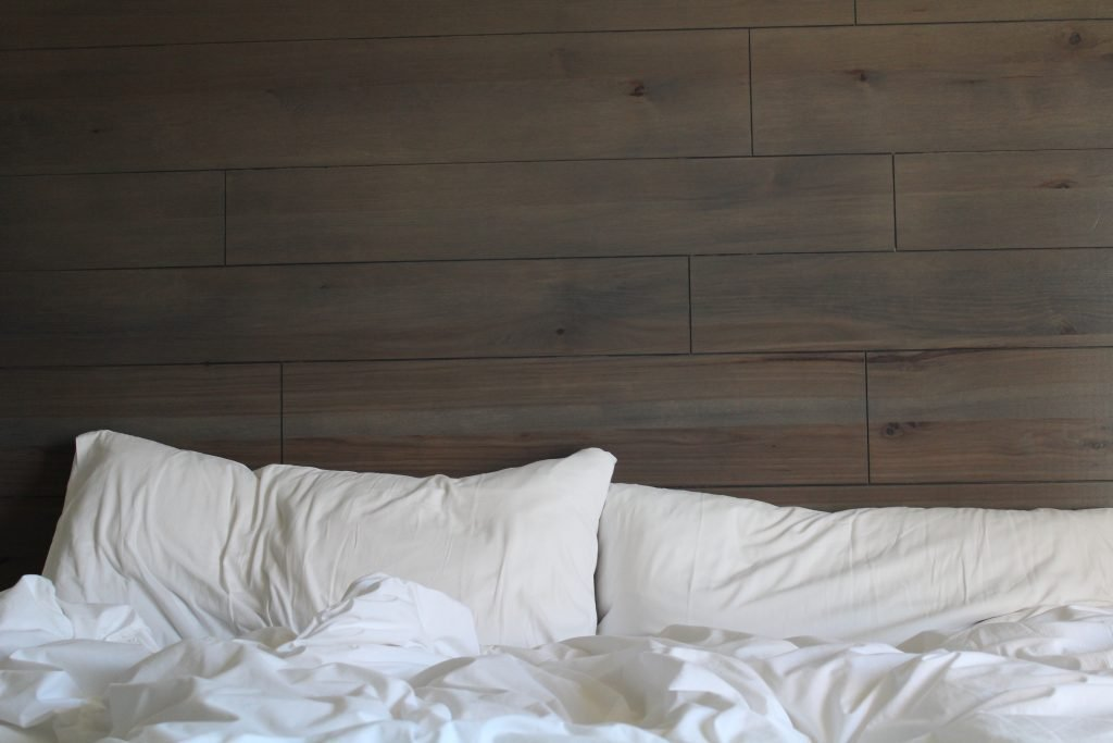 White bed sheets and a wood headboard.