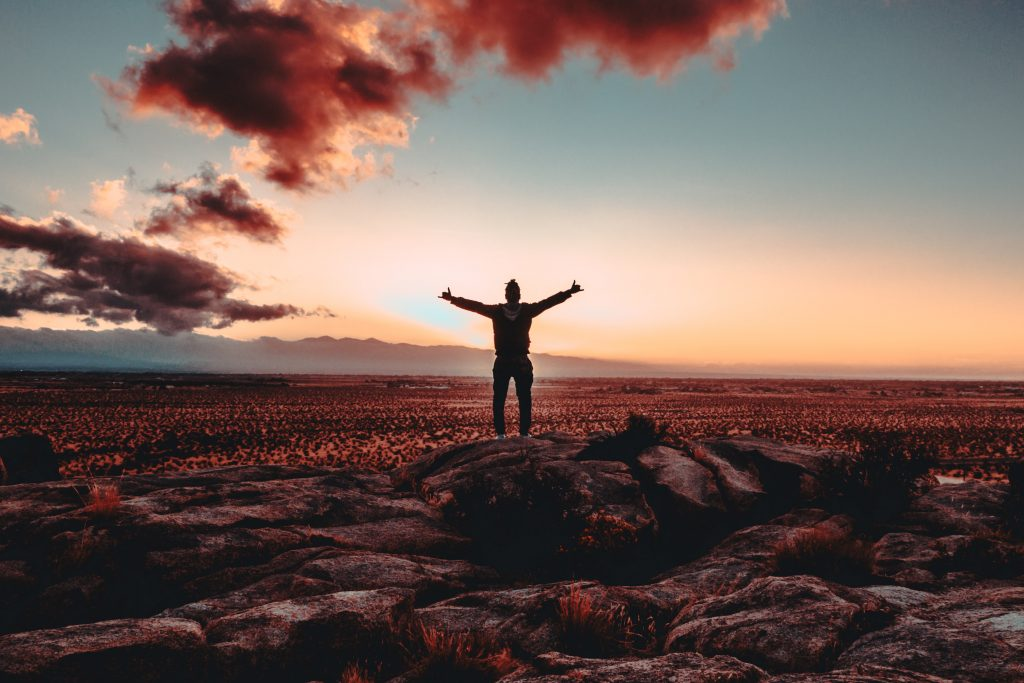 A silhouette of a person standing with their arms spread open wide. It's sunrise on a new day.