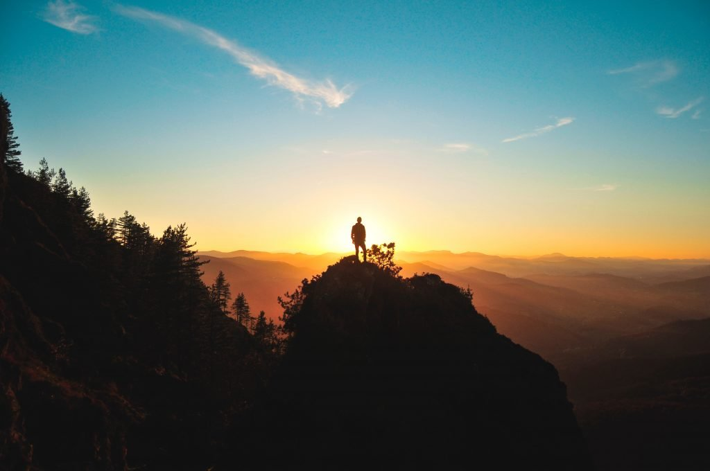 The silhouette of someone standing atop a mountain at sunrise.