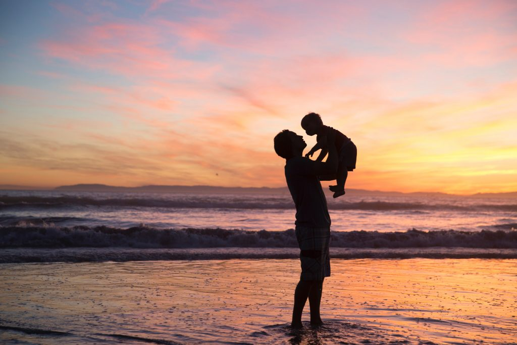 A silhouette of a father and baby at the beach.