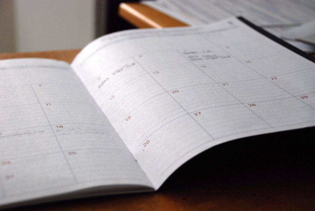 A white calendar opened up on a desk.