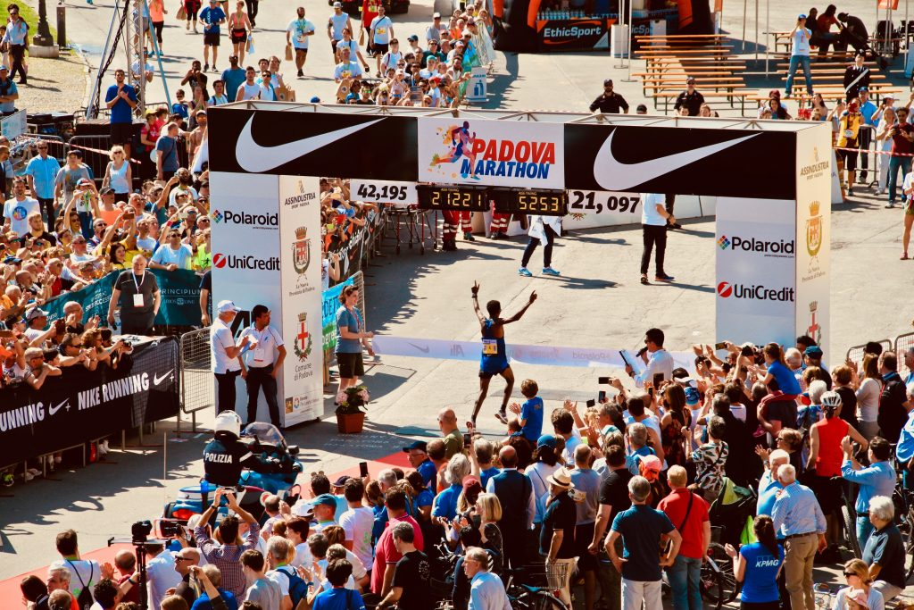 A person crossing the finish line of a marathon in victory.