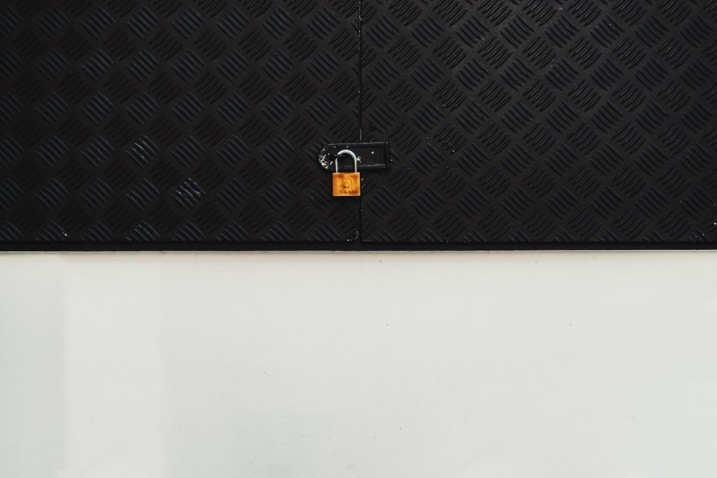 An orange lock on a black and white door.