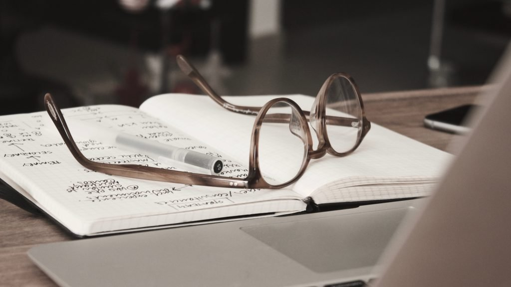 A pair of glasses resting on a notebook.