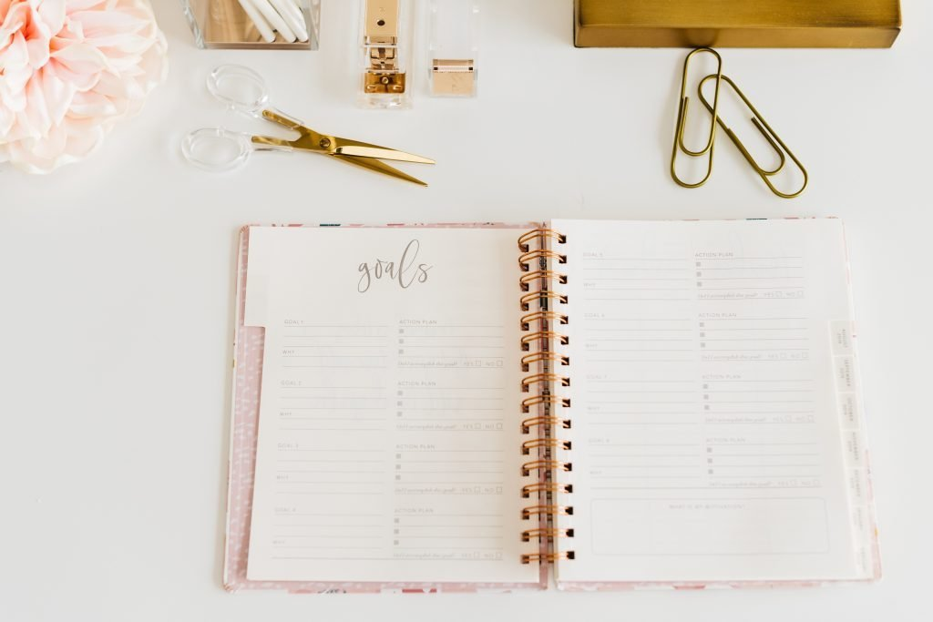 A gold notebook with gold scissors.
