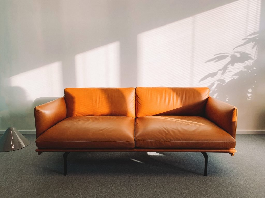 A brown leather sofa in a beige room.