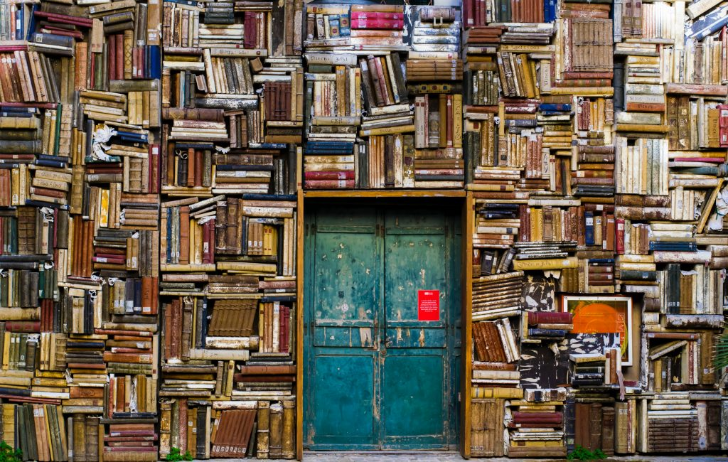 Many books surrounding a door.