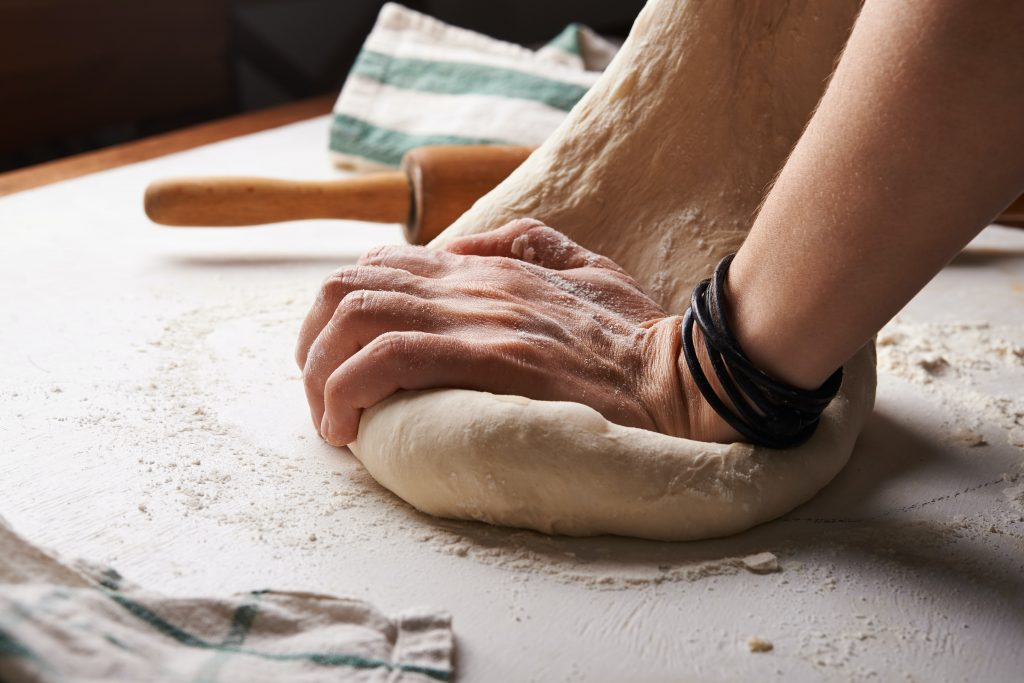 A person kneading dough.