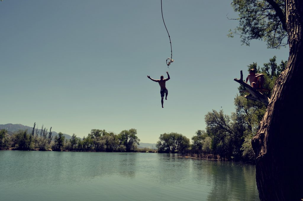 A person swinging from a rope into a lake.