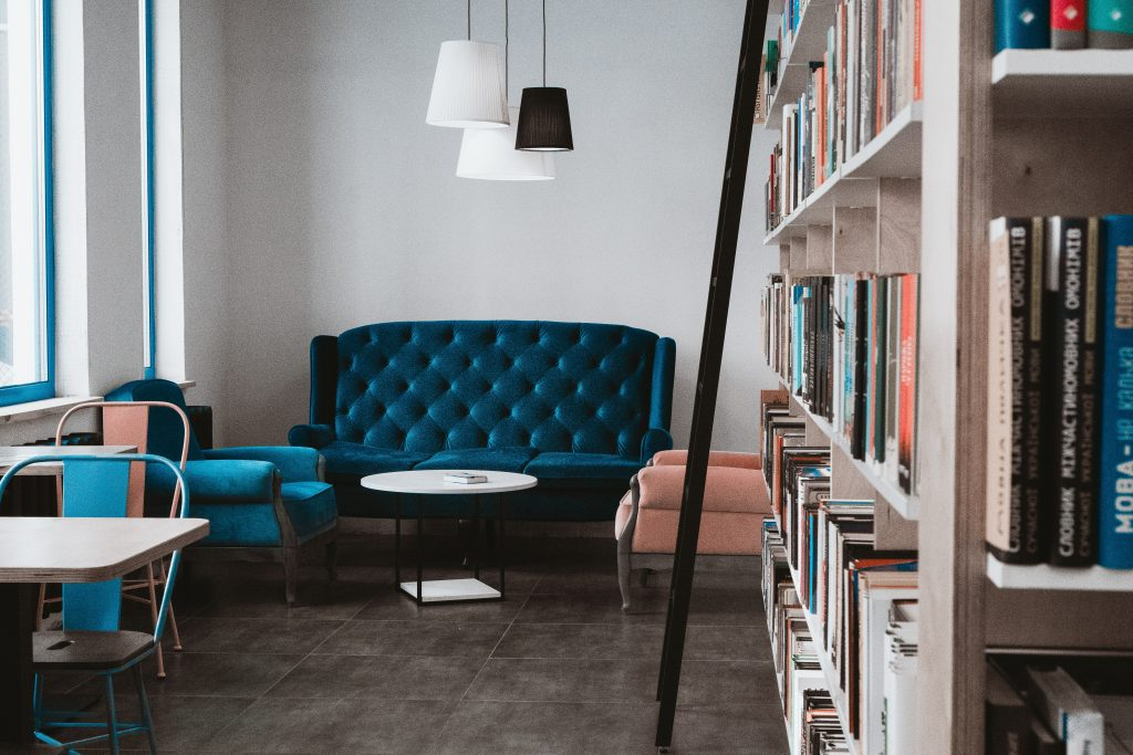 A blue couch in a library.