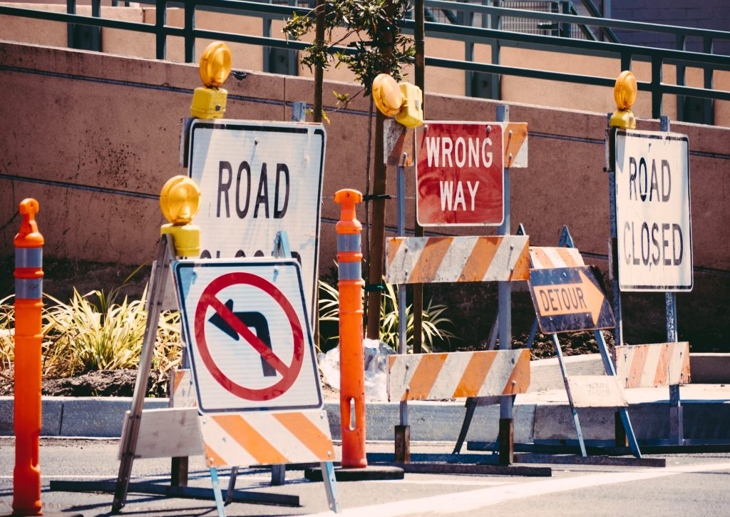 Various construction signs in the street.