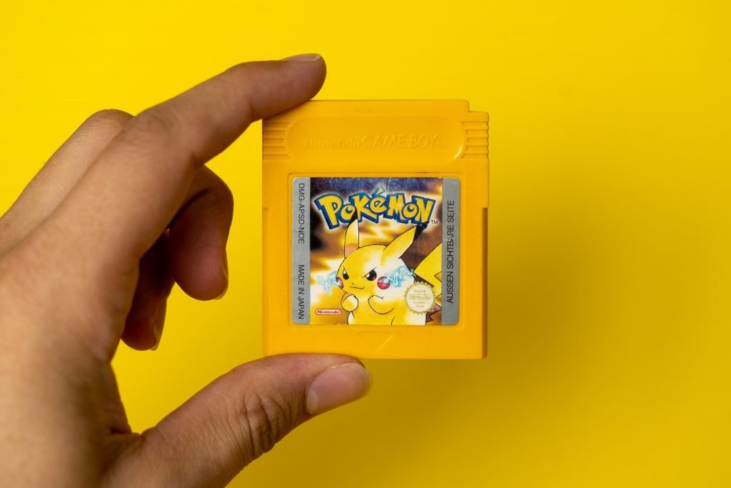 A person holding Pokemon Yellow.