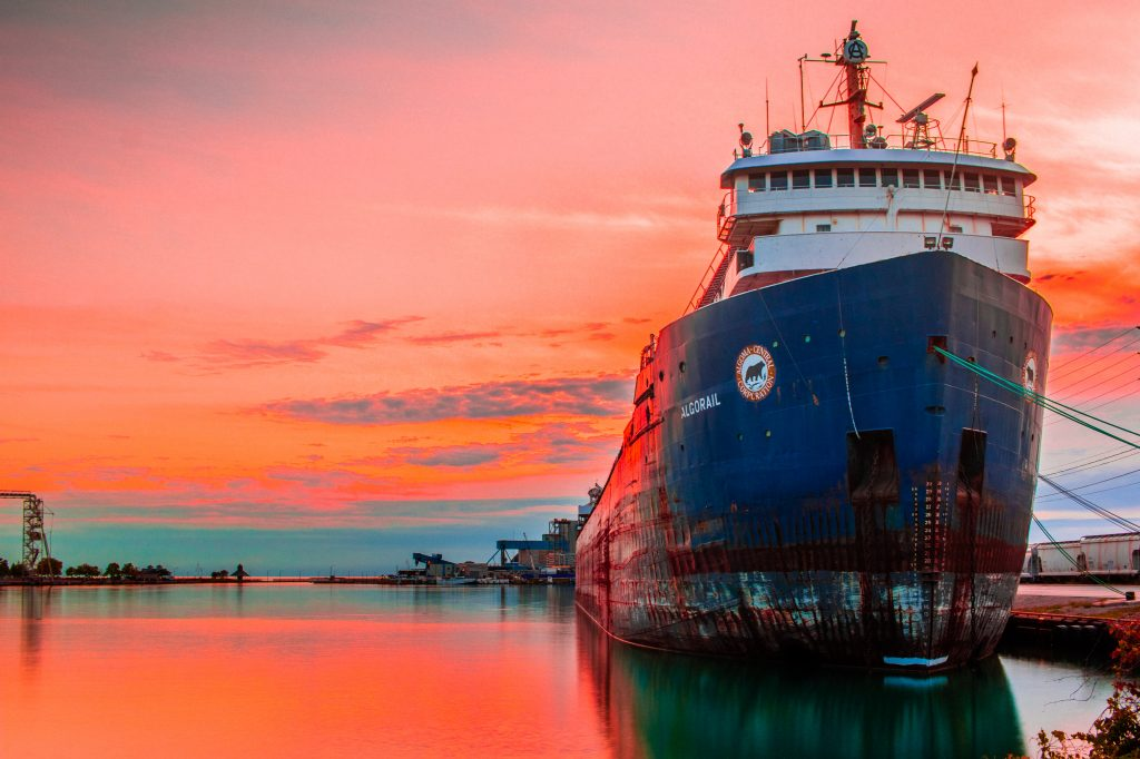 A massive ship in port during sunset.