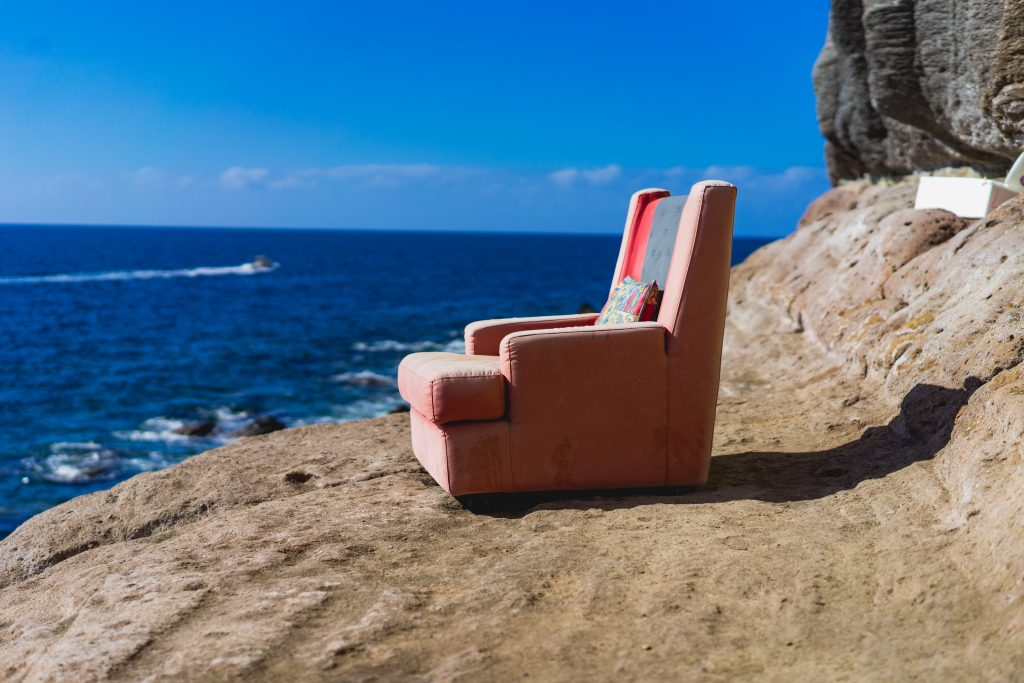 A recliner sitting on the beach.