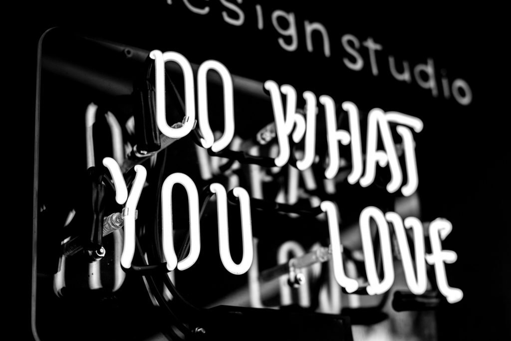"""A neon sign with the message, """"Do What You Love""""."""