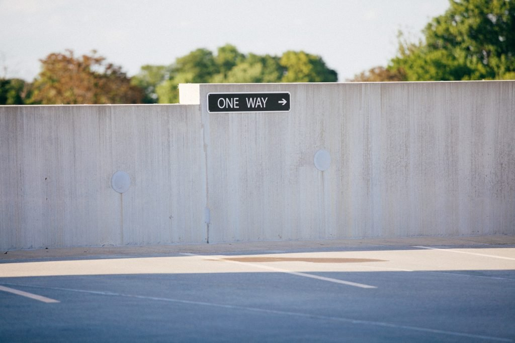 A one way sign on a grey wall.
