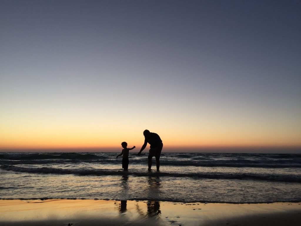 A parent and child in the ocean.