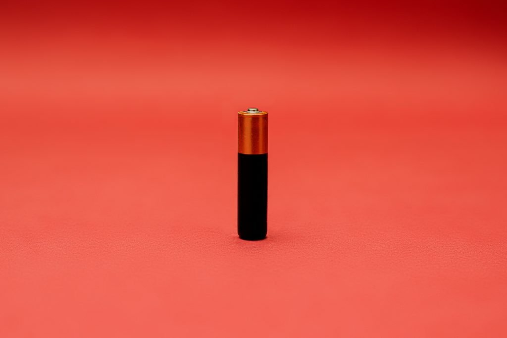 A battery on a red backdrop.