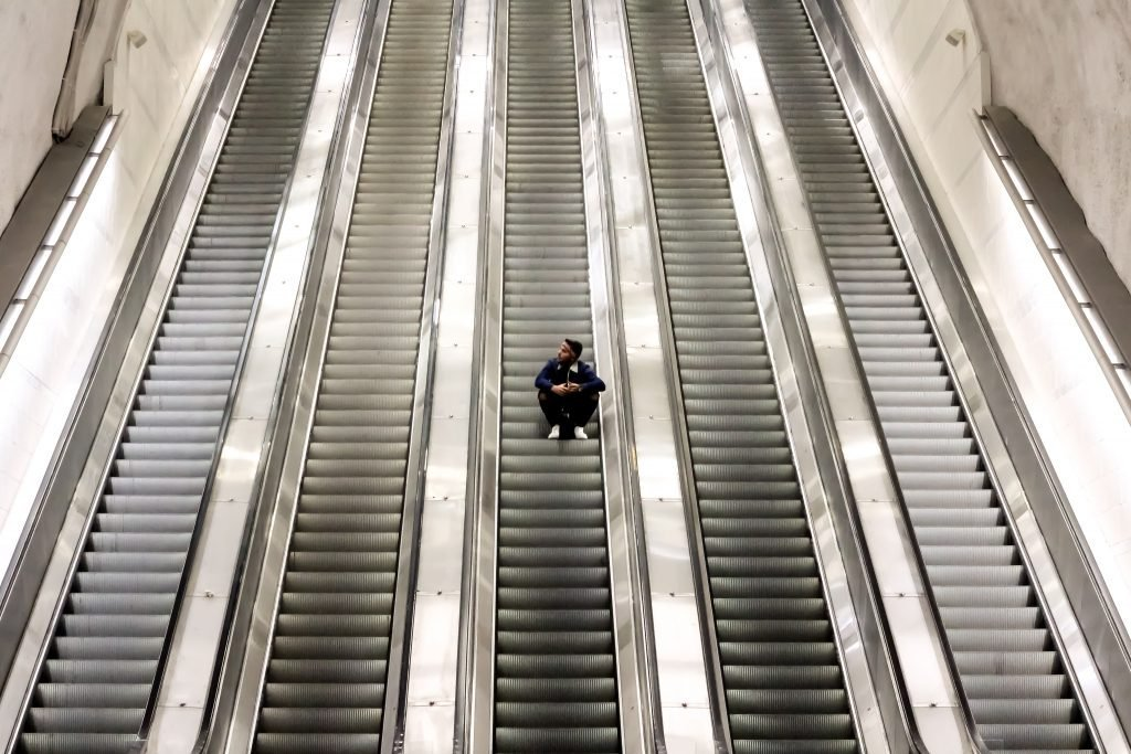 A person sitting in the middle of many stairs.