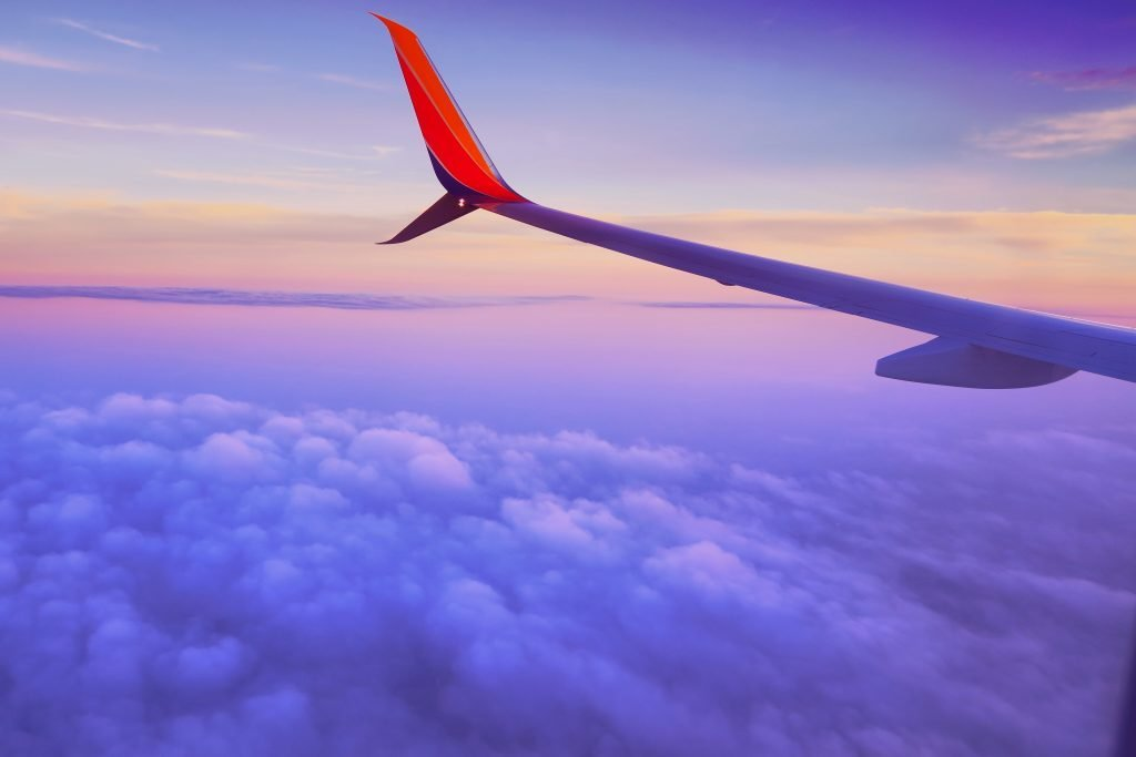 The wing of a plane in the air during sunset.