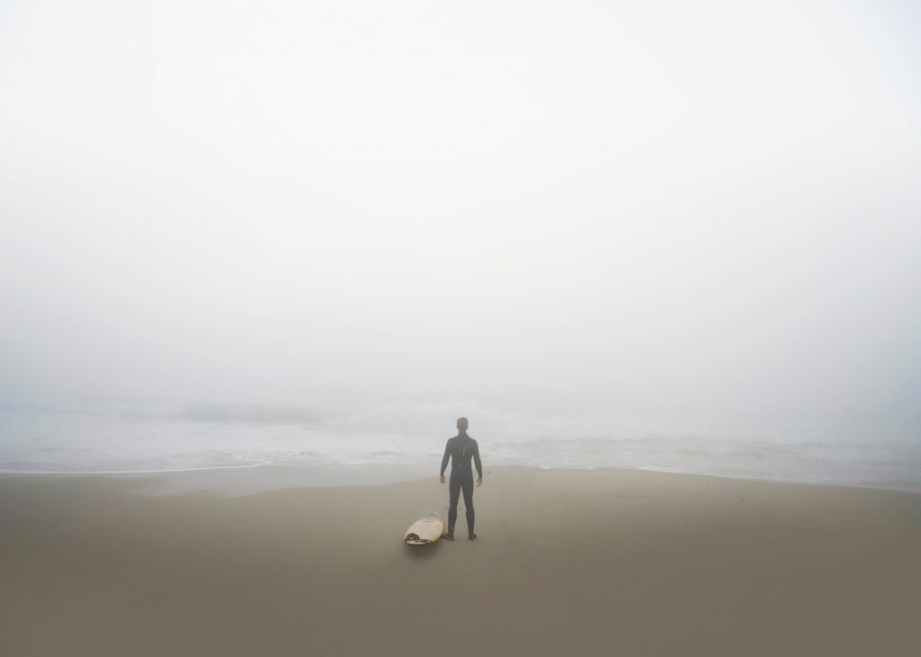 A surfer looking into the fog.