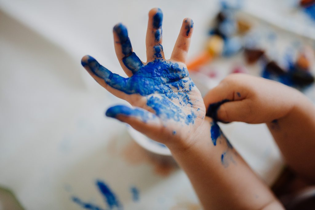 A kid with blue paint on their hands.