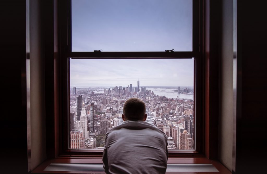 A person staring out a window in NYC.