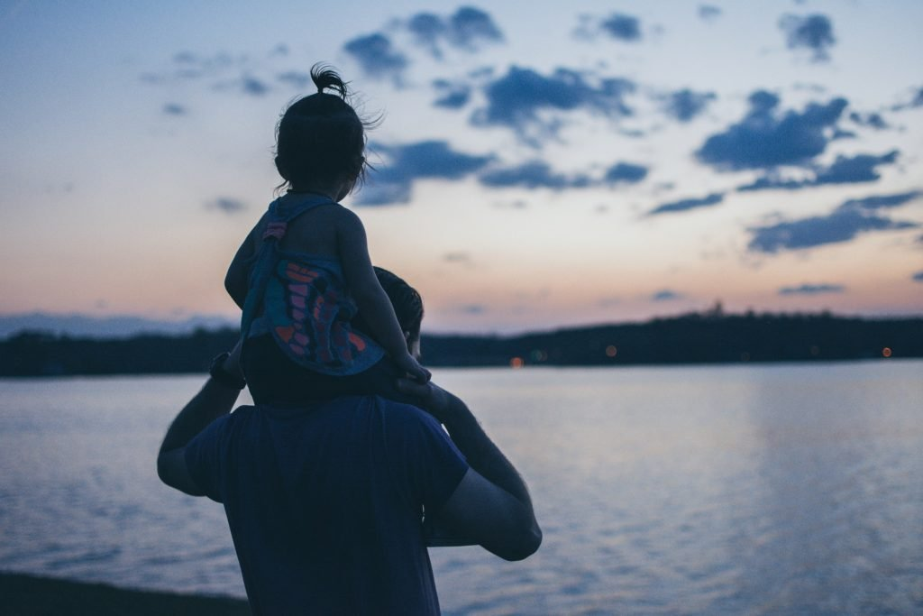 A daughter sitting on her parent's shoulders, looking at the water.