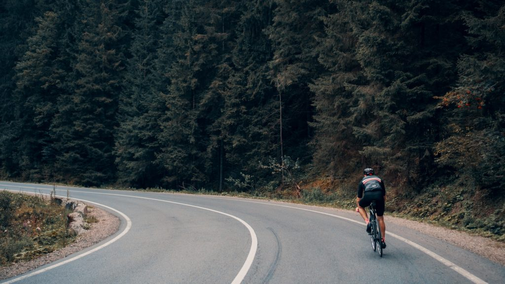 A person cycling alongside a forest.