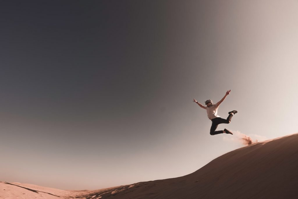 A person jumping from a sand dune.