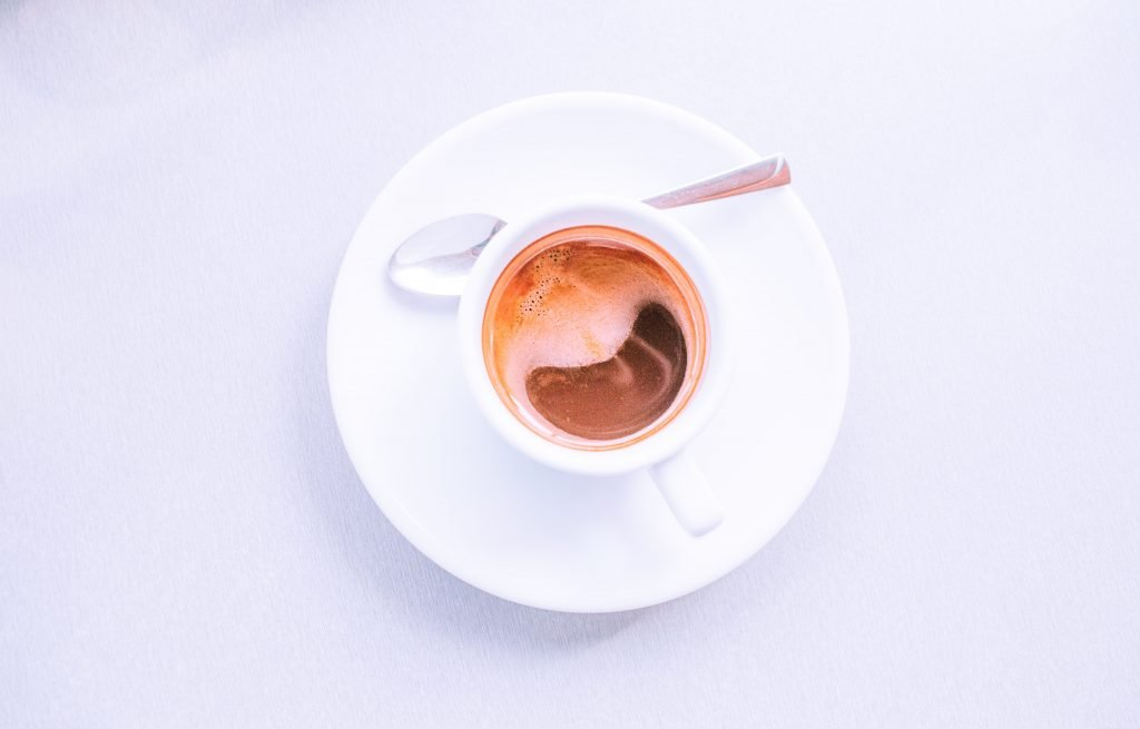 A white coffee cup on a white table.