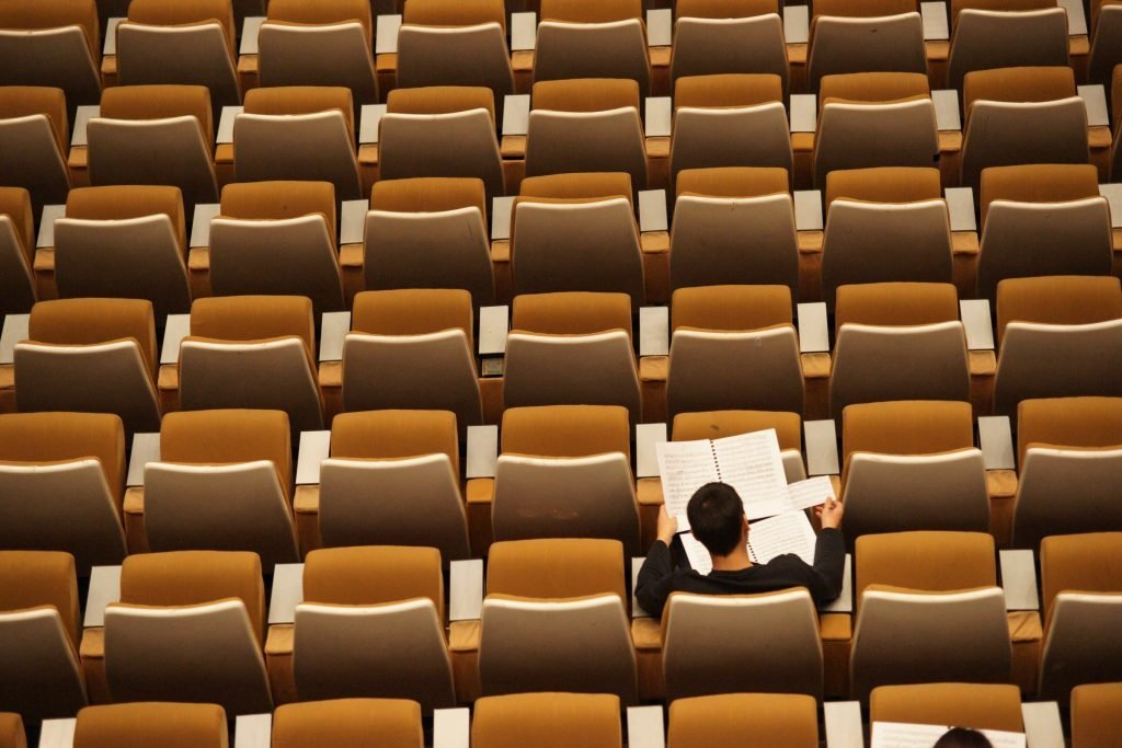 A person sitting among many chairs, staring at notes.