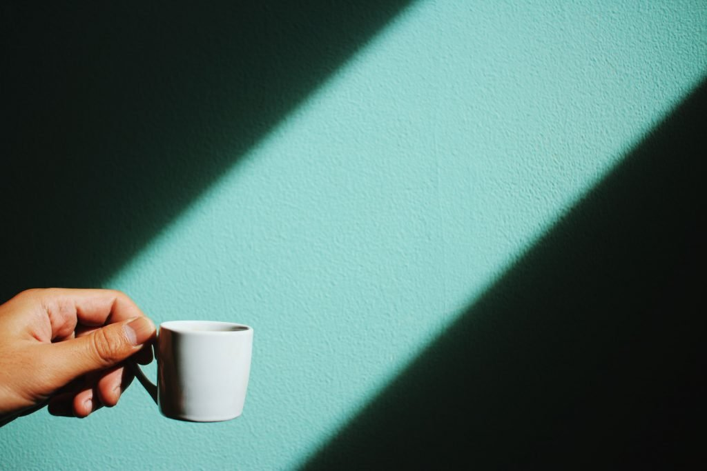 A person holding coffee next to a green wall.