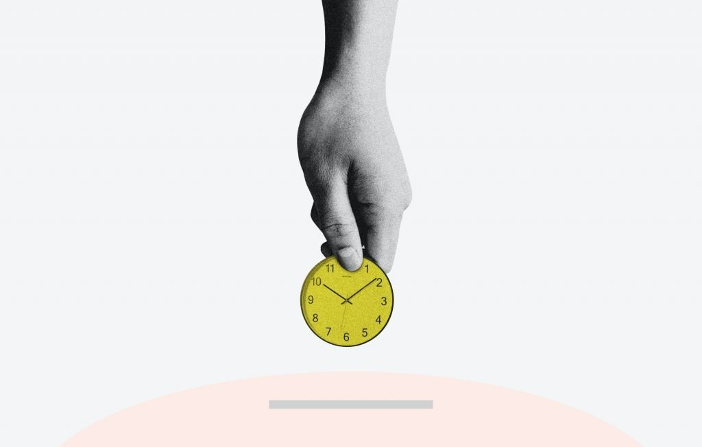 A hand holding a yellow clock.
