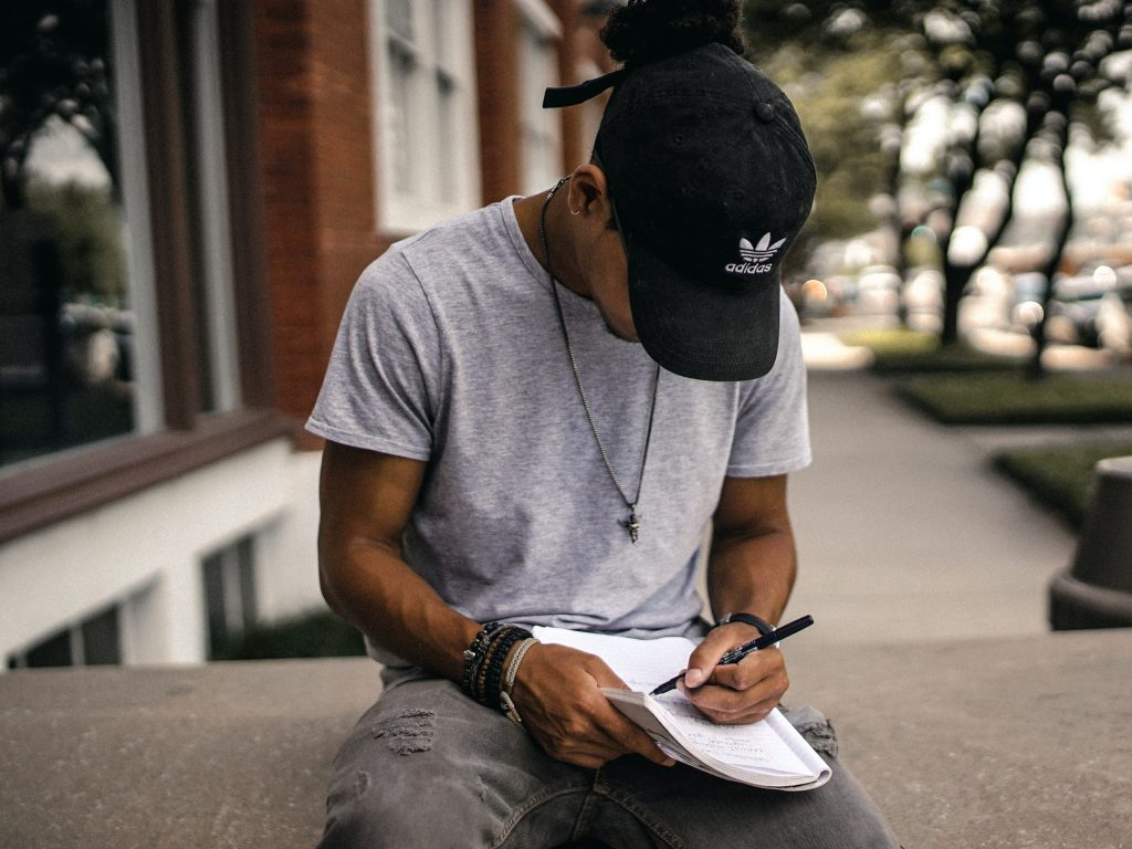 A person sitting on a ledge, writing.