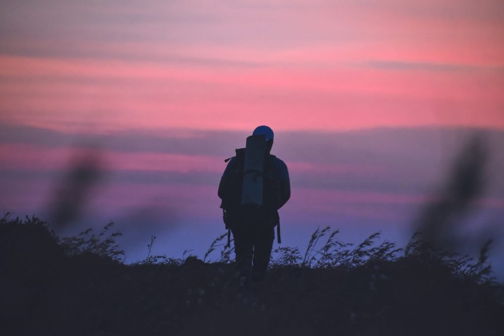 A person hiking through a meadow at sunset.