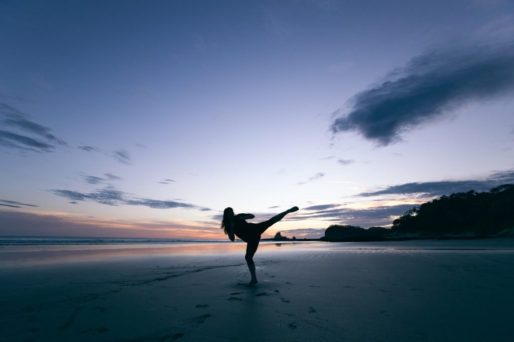 A person doing a kick at sunset.