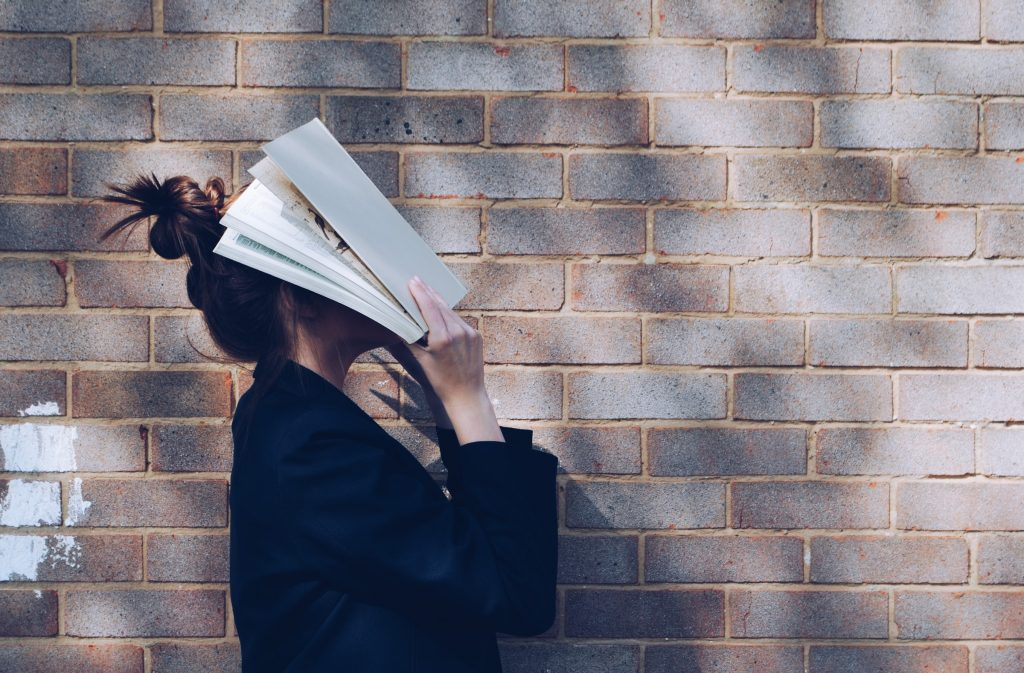 A woman with a book on her face.