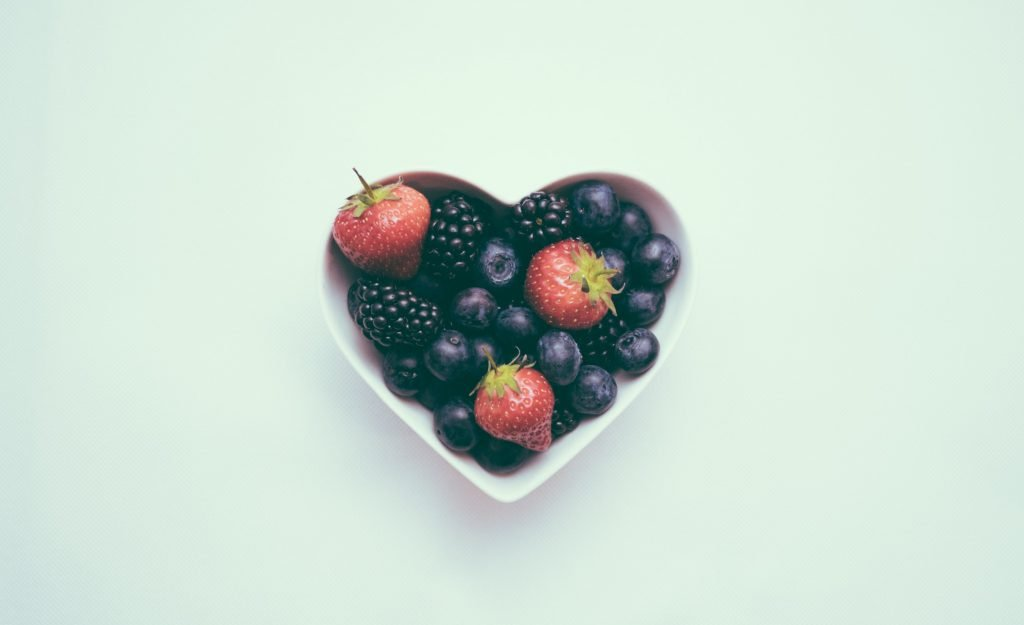 A heart-shaped bowl with fruit in it.