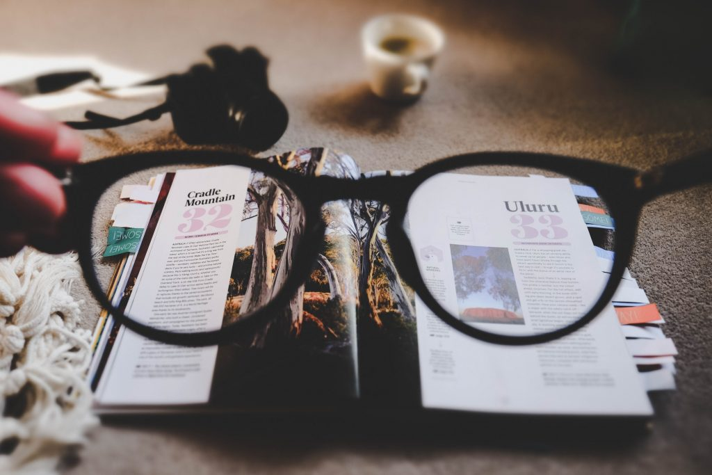 A pair of glasses pointed at a book.